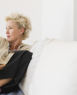 Mature woman sitting on sofa, looking away in thought